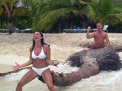 Bikini Girl hockt vor riesigem Palmenstamm