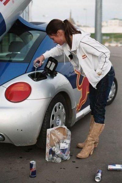 Brünettes Girl füllt Red Bull in den Tank ihres Autos