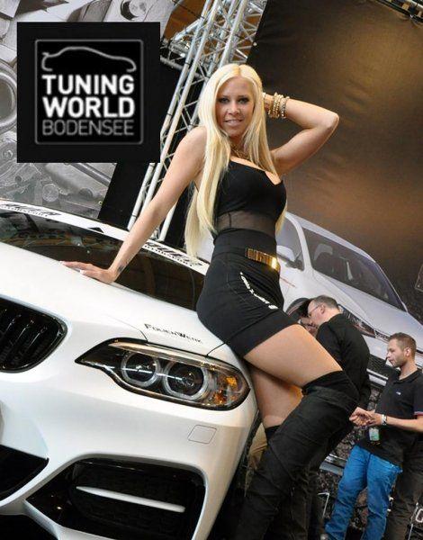 Sexy Blondine in Stiefeln posiert vor Tuning BMW