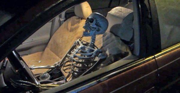 Skelett sitzt am Steuer eines Autos