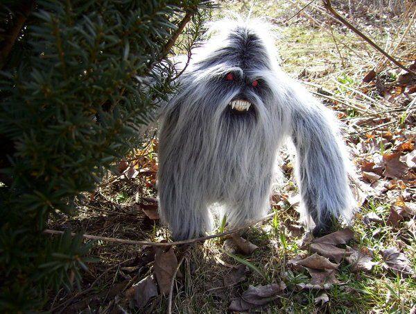 Haariges Monster mit scharfen Zähnen steht im Wald